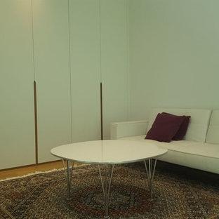 Ejemplo de vestidor unisex, actual, de tamaño medio, con armarios con paneles lisos, puertas de armario blancas, suelo laminado y suelo marrón