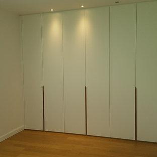 Foto de vestidor unisex, contemporáneo, de tamaño medio, con armarios con paneles lisos, puertas de armario blancas, suelo laminado y suelo marrón