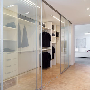 Exempel på ett stort modernt walk-in-closet för könsneutrala, med öppna hyllor, vita skåp och bambugolv