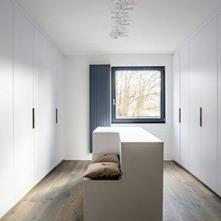 Neutrales, Großes Modernes Ankleidezimmer mit Ankleidebereich, flächenbündigen Schrankfronten, weißen Schränken, dunklem Holzboden und braunem Boden in Dortmund