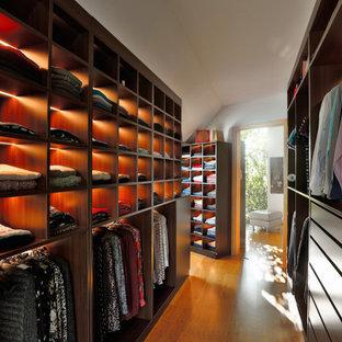 Imagen de armario vestidor moderno, extra grande, con armarios abiertos, suelo de bambú y suelo marrón