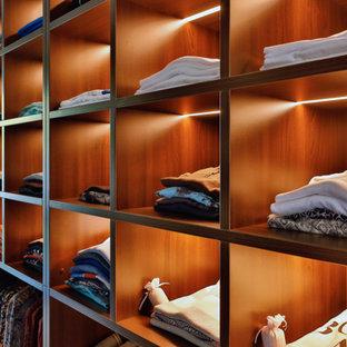 Imagen de armario vestidor minimalista, extra grande, con armarios abiertos, suelo de bambú y suelo marrón