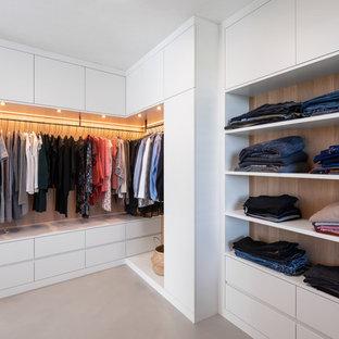 Aménagement d'un très grand dressing scandinave neutre avec un placard à porte plane, des portes de placard blanches, béton au sol et un sol gris.
