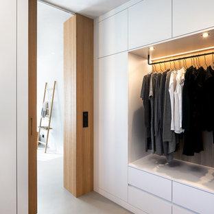 Neutraler Nordischer Begehbarer Kleiderschrank mit flächenbündigen Schrankfronten, weißen Schränken, Betonboden und grauem Boden in München