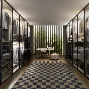 Idee per una grande cabina armadio unisex design con ante di vetro, ante nere, parquet scuro e pavimento marrone
