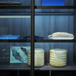 Diseño de armario vestidor unisex, contemporáneo, extra grande, con armarios tipo vitrina, puertas de armario blancas, suelo de madera oscura y suelo marrón