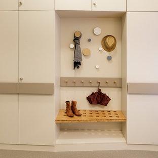 Inredning av ett skandinaviskt mellanstort omklädningsrum för könsneutrala, med släta luckor, vita skåp, linoleumgolv och beiget golv