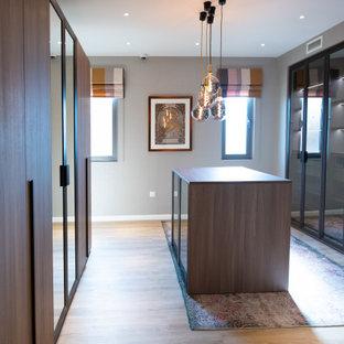 Foto de armario vestidor unisex, actual, extra grande, con armarios con paneles lisos, puertas de armario de madera en tonos medios, suelo vinílico y suelo marrón