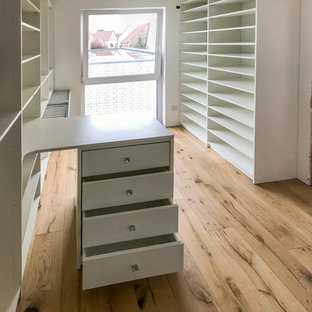 Diseño de armario vestidor unisex, actual, de tamaño medio, con armarios abiertos, puertas de armario blancas, suelo de madera pintada y suelo beige