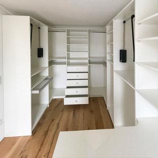 Ispirazione per una cabina armadio unisex design di medie dimensioni con nessun'anta, ante bianche, pavimento in legno verniciato e pavimento beige