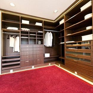 Idee per una grande cabina armadio unisex classica con nessun'anta, ante in legno bruno e moquette