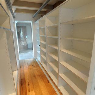 Foto de armario vestidor contemporáneo, pequeño, con armarios tipo vitrina, puertas de armario blancas, suelo de madera clara y suelo marrón
