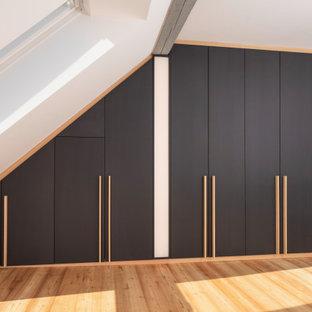 Immagine di una cabina armadio unisex moderna di medie dimensioni con ante lisce, ante nere, parquet chiaro, pavimento marrone e travi a vista
