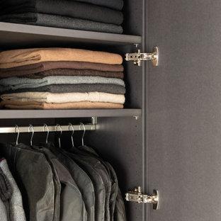 Réalisation d'un dressing minimaliste de taille moyenne et neutre avec un placard à porte plane, des portes de placard noires, un sol en bois clair, un sol marron et un plafond en poutres apparentes.