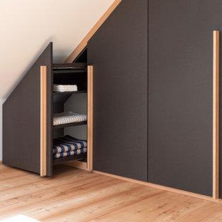 Idéer för ett mellanstort modernt walk-in-closet för könsneutrala, med släta luckor, svarta skåp, ljust trägolv och brunt golv