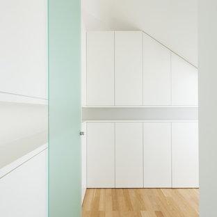 Idéer för att renovera ett funkis omklädningsrum, med släta luckor, vita skåp och ljust trägolv