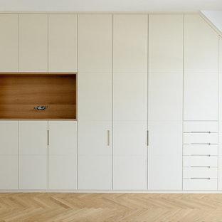 Ejemplo de vestidor unisex, actual, extra grande, con armarios con paneles lisos, puertas de armario beige, suelo de madera clara y suelo beige