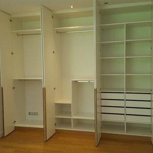 Foto di uno spazio per vestirsi unisex minimal di medie dimensioni con ante lisce, ante bianche, pavimento in laminato e pavimento marrone