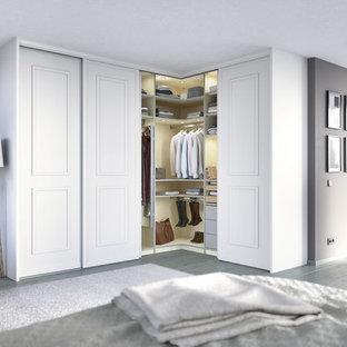 Ejemplo de armario unisex, contemporáneo, pequeño, con armarios con paneles con relieve, puertas de armario blancas, suelo de madera clara y suelo gris