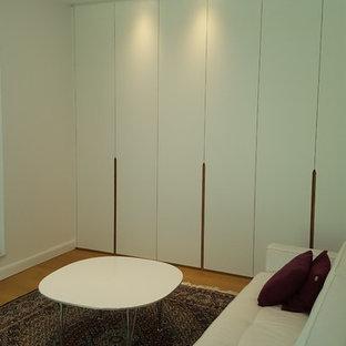 Immagine di uno spazio per vestirsi unisex minimal di medie dimensioni con ante lisce, ante bianche, pavimento in laminato e pavimento marrone