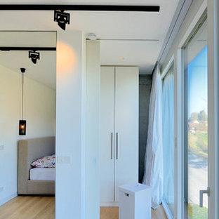 Neutraler Moderner Begehbarer Kleiderschrank Mit Flächenbündigen  Schrankfronten, Weißen Schränken Und Braunem Holzboden In München