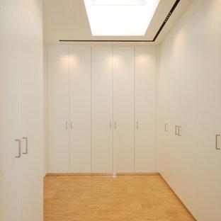 Foto di un armadio o armadio a muro moderno di medie dimensioni con ante lisce, ante bianche, pavimento in bambù e pavimento beige