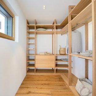 Ejemplo de armario vestidor unisex, nórdico, de tamaño medio, con armarios abiertos, suelo de madera oscura y puertas de armario beige