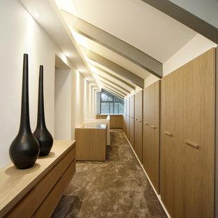 Foto di un'ampia cabina armadio unisex minimalista con ante lisce, ante in legno chiaro e moquette