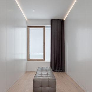 Foto de vestidor unisex, moderno, de tamaño medio, con armarios con paneles lisos, puertas de armario blancas, suelo de madera clara y suelo beige