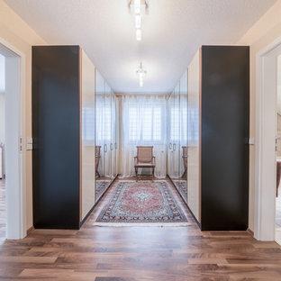 Foto de armario vestidor unisex, exótico, con armarios con paneles lisos, puertas de armario beige, suelo de madera en tonos medios y suelo marrón