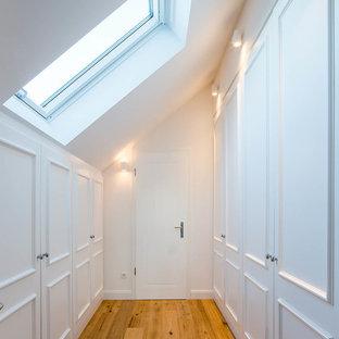 Klassisk inredning av ett mellanstort walk-in-closet för könsneutrala, med luckor med profilerade fronter, vita skåp, mellanmörkt trägolv och brunt golv