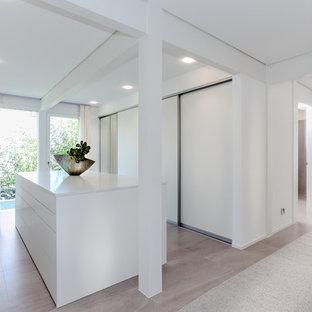 Großer, Neutraler Moderner Begehbarer Kleiderschrank mit flächenbündigen Schrankfronten, weißen Schränken, Keramikboden und beigem Boden in Sonstige