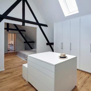 Neutraler, Großer Moderner Begehbarer Kleiderschrank mit flächenbündigen Schrankfronten, weißen Schränken, braunem Holzboden und braunem Boden in Köln