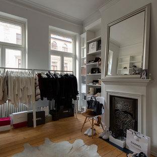 Foto di uno spazio per vestirsi per donna industriale di medie dimensioni con nessun'anta, ante bianche, parquet chiaro e pavimento beige