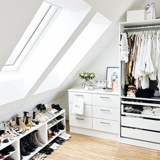 Cette image montre un dressing room nordique de taille moyenne pour une femme avec un placard à porte plane, des portes de placard blanches, un sol en bois clair et un sol beige.