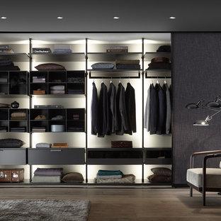 Imagen de vestidor de hombre, contemporáneo, de tamaño medio, con armarios abiertos, suelo de madera en tonos medios y suelo marrón