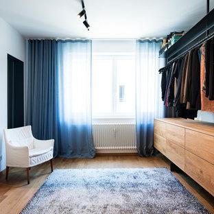 Neutrales, Mittelgroßes Modernes Ankleidezimmer mit Ankleidebereich, flächenbündigen Schrankfronten, hellbraunen Holzschränken, braunem Holzboden und braunem Boden in München