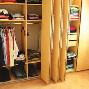 Ejemplo de armario de hombre, actual, de tamaño medio, con armarios con paneles lisos, puertas de armario de madera oscura, moqueta y suelo amarillo