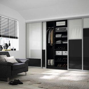 Modelo de armario clásico, grande, con armarios tipo vitrina, puertas de armario negras, suelo de madera clara y suelo marrón