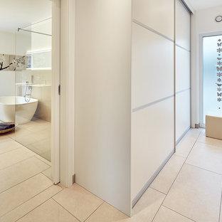 Foto de armario vestidor unisex, escandinavo, pequeño, con armarios con paneles lisos, puertas de armario blancas, suelo de baldosas de cerámica y suelo beige