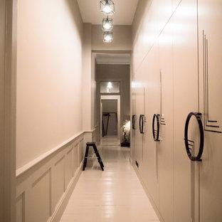 Inspiration för ett mellanstort eklektiskt walk-in-closet för könsneutrala, med släta luckor, vita skåp och ljust trägolv