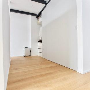 Imagen de armario unisex, minimalista, de tamaño medio, con armarios con paneles lisos, puertas de armario grises, suelo de madera clara y suelo amarillo