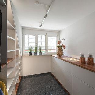 Foto di una cabina armadio unisex contemporanea di medie dimensioni con ante lisce, ante bianche e pavimento nero
