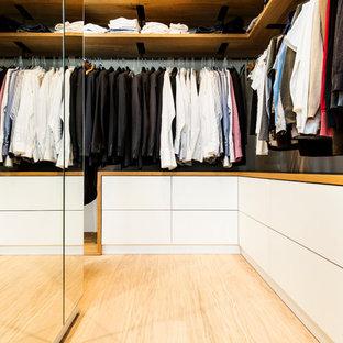 Ejemplo de armario vestidor de hombre, contemporáneo, de tamaño medio, con puertas de armario blancas, suelo de madera clara, armarios con paneles lisos y suelo beige