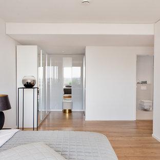 Diseño de vestidor unisex, actual, pequeño, con armarios con paneles lisos, puertas de armario blancas, suelo de madera en tonos medios y suelo marrón