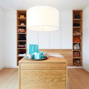 Mittelgroßes Modernes Ankleidezimmer mit Ankleidebereich, flächenbündigen Schrankfronten, weißen Schränken, braunem Holzboden und braunem Boden