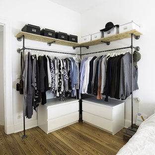 Photo of a large industrial gender-neutral walk-in wardrobe in Hamburg with open cabinets, medium hardwood floors, white cabinets and brown floor.