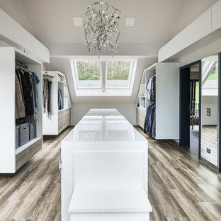 Diseño de vestidor de hombre, contemporáneo, extra grande, con armarios abiertos, puertas de armario blancas y suelo de madera en tonos medios
