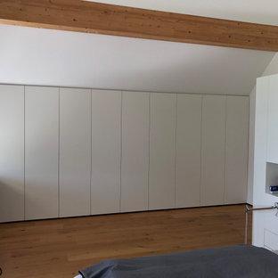 Modelo de armario y vestidor actual, grande, con armarios con paneles lisos, puertas de armario blancas, suelo de madera en tonos medios y suelo marrón