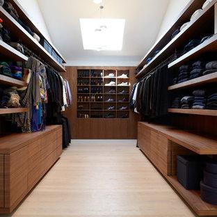 Diseño de armario vestidor unisex, moderno, de tamaño medio, con armarios abiertos, puertas de armario marrones y suelo de madera clara